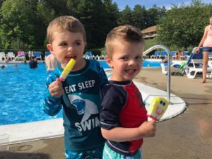 Toddlers eating ice cream by a pool.