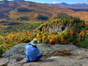 man takes photo of fall foliage