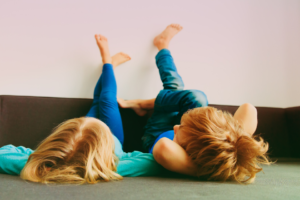 two young kids lying down with feet on the wall -- how to talk to young kids about sexism