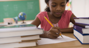 young girl writing - writing strategies for kids