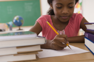 young girl writing - helping kids with writing assignments
