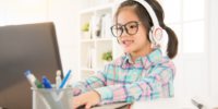online learning resources for kids - girl at computer with headphones