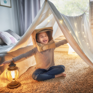 child in living room tent