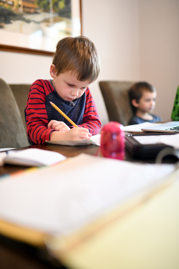 boy with pencil working at table -- local resources for homeschooling in New Hampshire