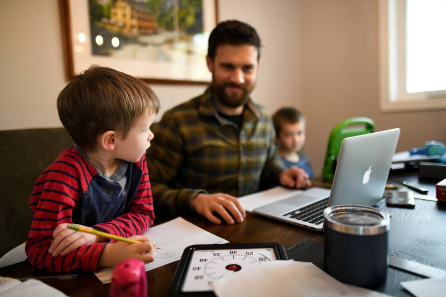 father at table with computer and two young sons - tips for homeschooling