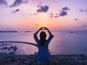 building balance in busy lives - woman sitting on rocks by ocean, arms overhead making a heart with her hands