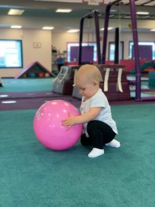 Baby playing with a pink ball - Safe Social Interaction on the Seacoast