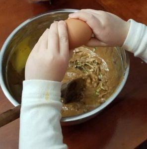 little kid hands breaking egg over bowl. Curbing the constant snacking by getting your kids in the ktichen