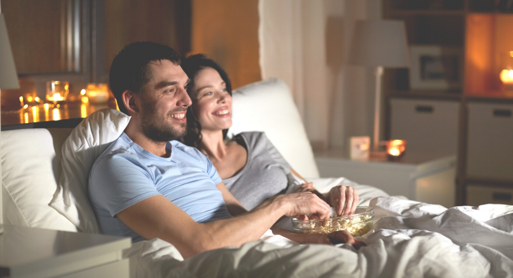 a couple snuggling on the couch watching date-night comedies