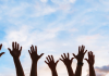 hands reaching up into the air volunteering with your kids on the Seacoast