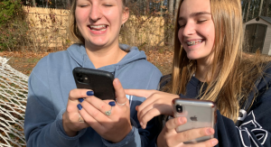 Two teenage girls laughing while looking at their cell phones.- kids' screen time