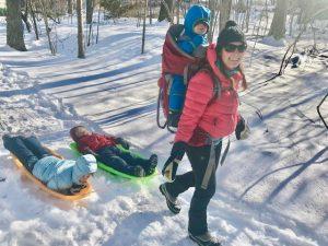 Mom pulls kids on sled