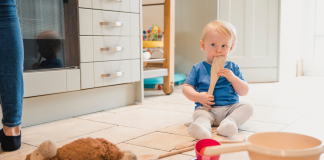 Toddler sitting on the kitchen floor playing with a wooden spoon, other kitchen items and a stuffed animal. Keep your baby entertained with treasure baskets.