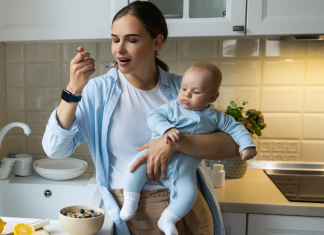 Photo of a mom eating over the sink while holding a baby. Postpartum nutrition isn't easy.