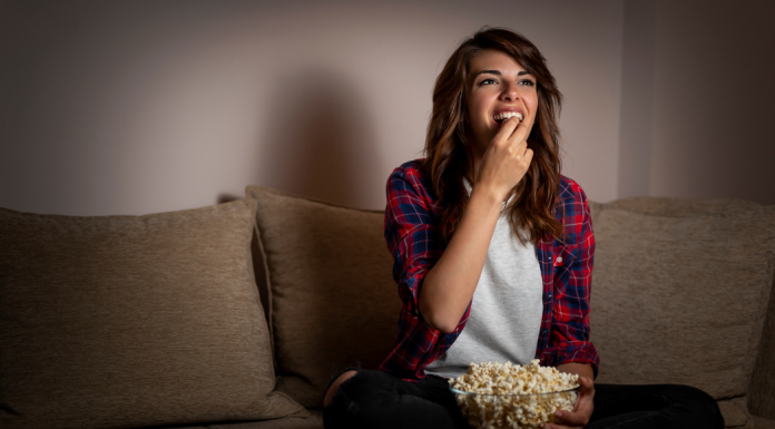 Woman eating popcorn on couch - best shows you aren't watching
