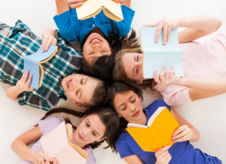tweens lying in circle with heads together looking at books