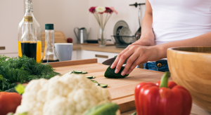 woman's hands cutting a cucumber on a cutting board - meal delivery services