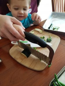 parent and toddler using a children's knife together - getting kids to eat salad