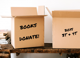 """Spring cleaning, stack of books and cardboard boxes marked """"Books Donate"""" and """"Boys 3T and 4T"""""""