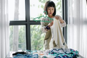 Little girl sorting clothes for spring cleaning