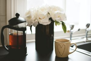 Spring cleaning mug with heart, tea pot, and vase of flowers