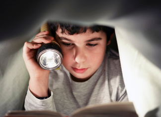 Young reader holding a flashlight and reading a story for book lovers under the covers.