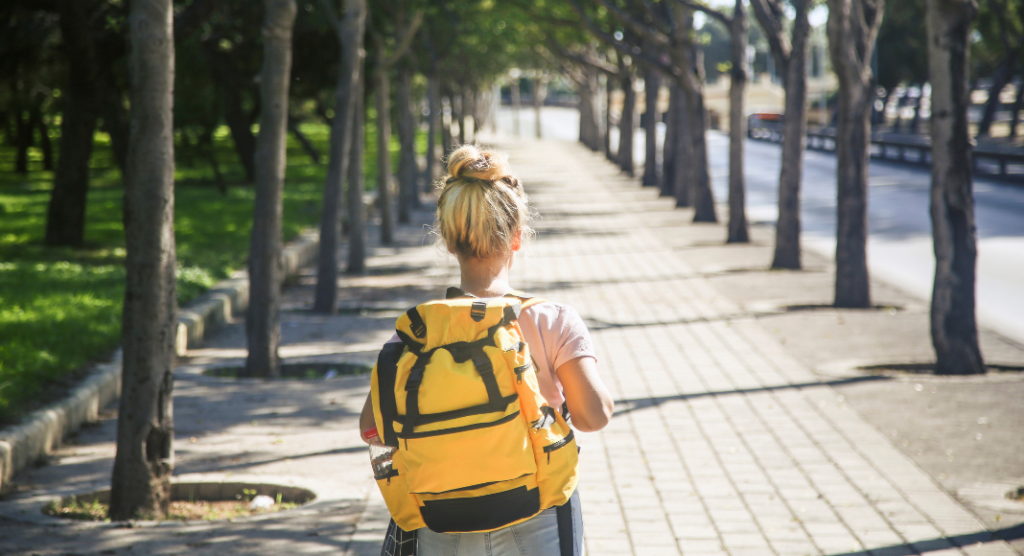 girl walking down road with yellow backpack
